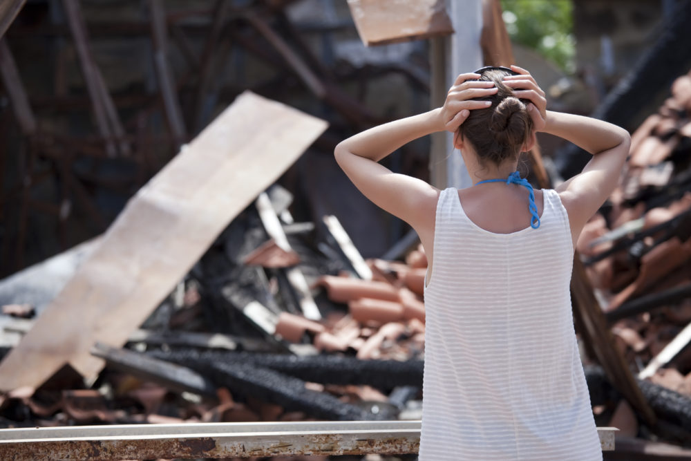 woman reacting to the fire damage done to her home