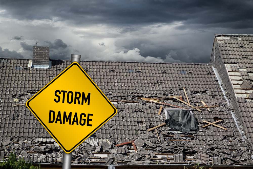 a hurricane damaged roof behind a sign warning of storm damage