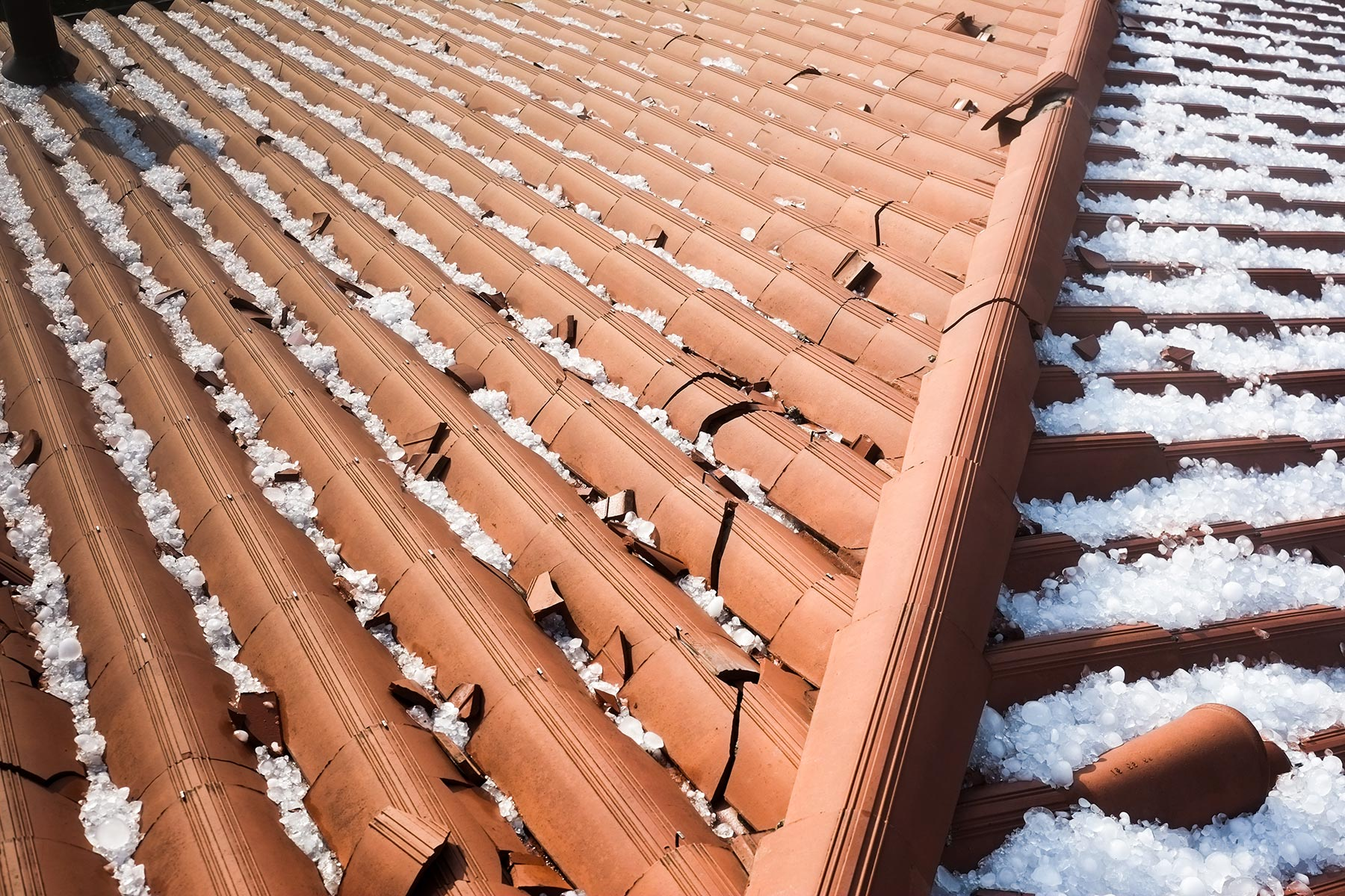 Damaged rooftop covered in hail after a hail storm