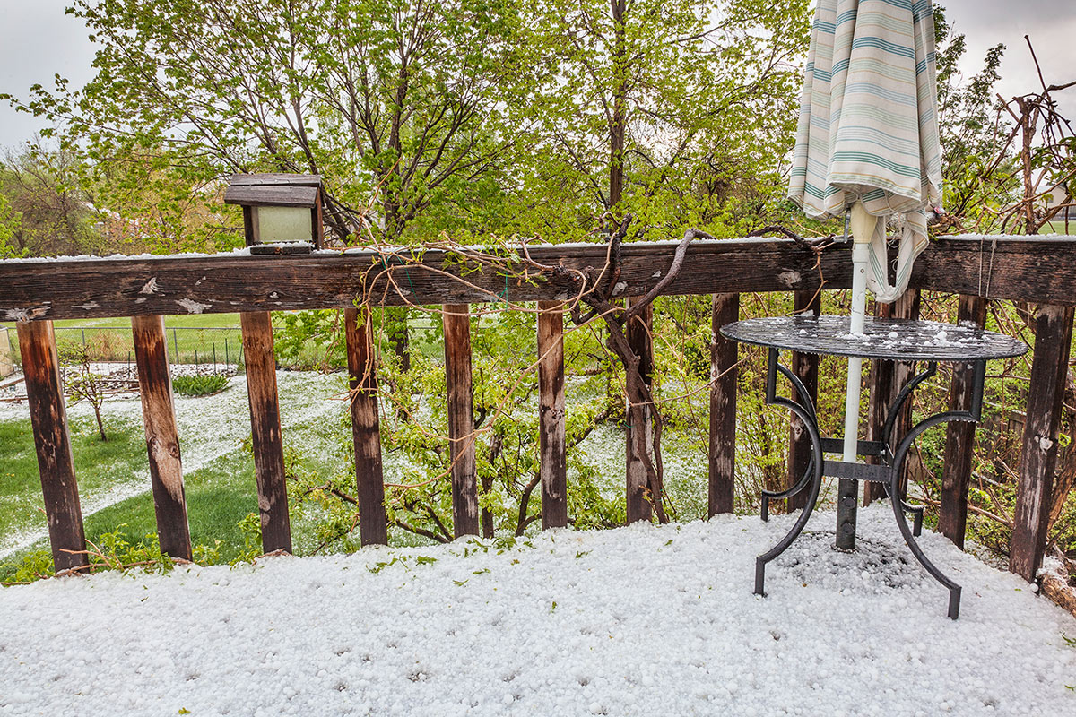 Damaged porch and table covered in hail after storm