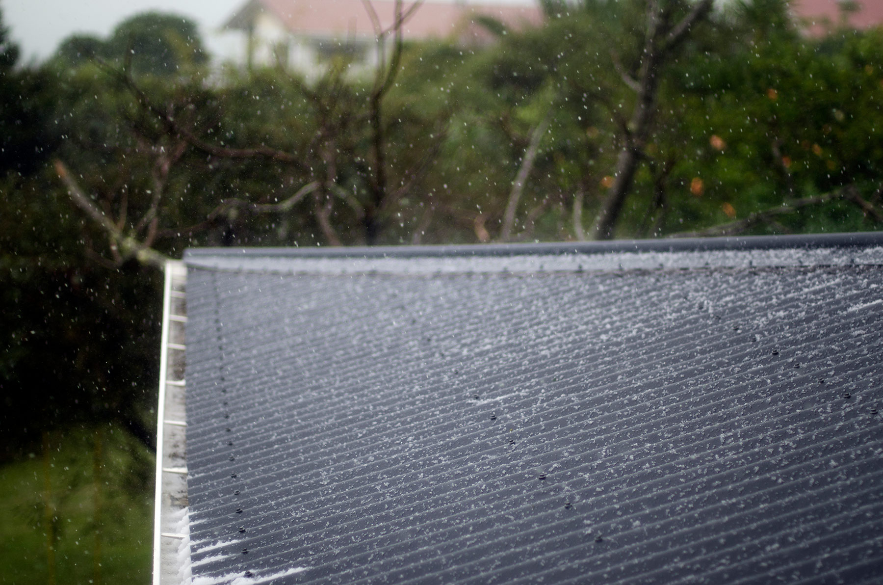 Rooftop being struck with hail during a hail storm