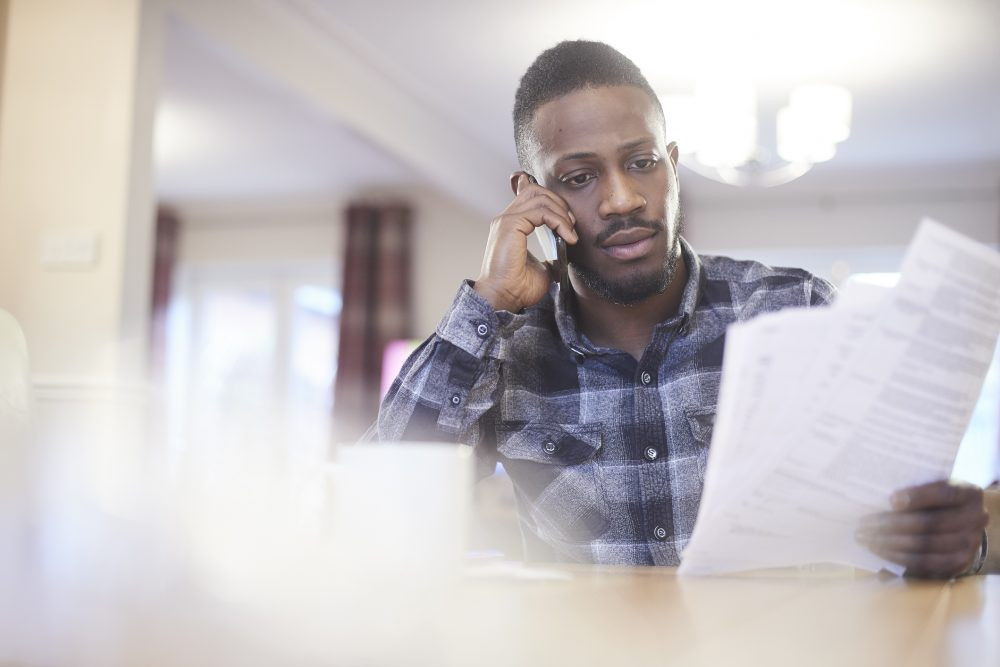 A homeowner on the phone with his disaster insurance claims attorney.